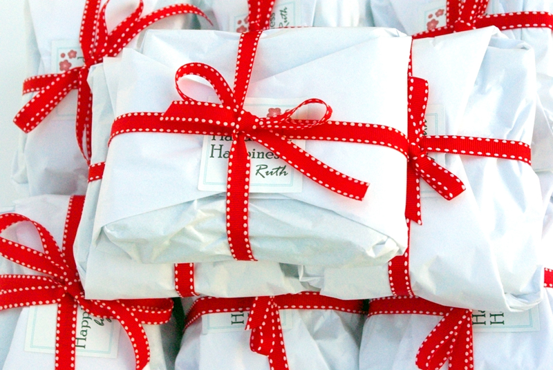 Soft toys come wrapped in bright white tissue paper with a red ribbon.